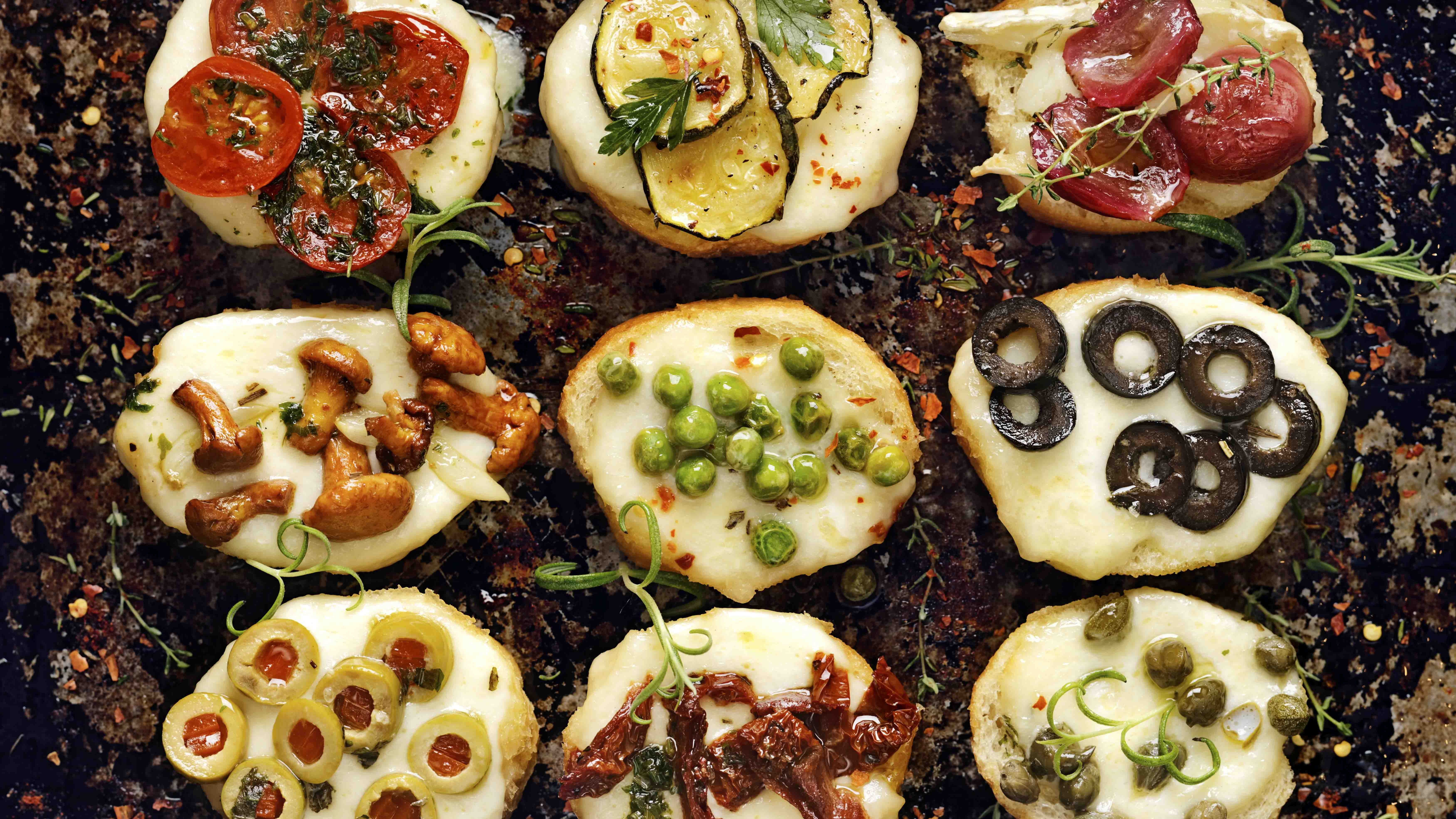 Crostini with different toppings on dark background. Delicious v